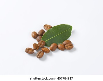 handful of roasted coffee beans with leaf on white background