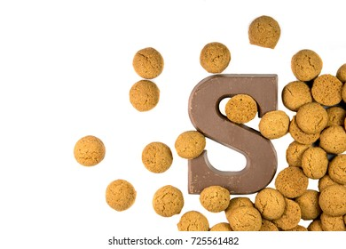 Handful of Scattered Pepernoten cookies with chocolate letter as Sinterklaas decoration on white background for dutch sinterklaasfeest holiday event on december 5th