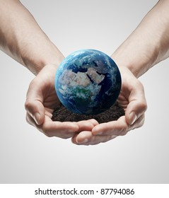 Handful soil with the Earth in the male hands. Conceptual symbol of the Earth with human hands. On a gray background