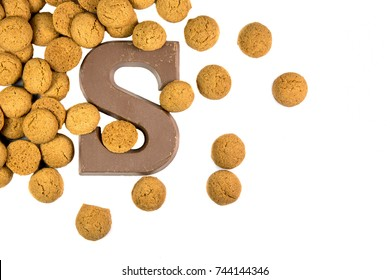 Handful of thrown Pepernoten cookies with chocolate letter as Sinterklaas decoration on white background for dutch sinterklaasfeest holiday event on december 5th