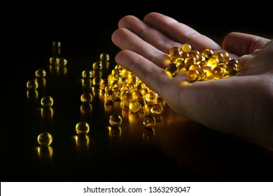 A handful of yellow transparent oil-based capsules in a man's hand on a black background. Vitamins. Omega-3. Fish oil capsules. D3.