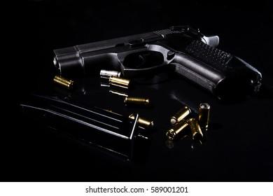handgun with ammunition on black surface