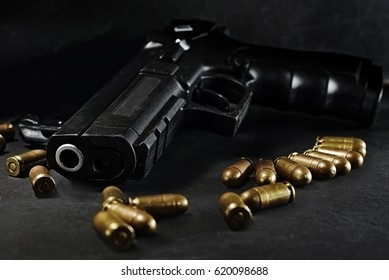 handgun with ammunition on a black surface, photographed on low light