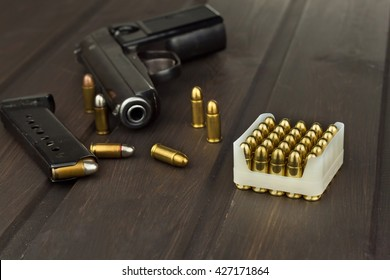 Handgun with ammunition on a dark wooden table. Sales of weapons and ammunition. Advertising on ammunition. New gun and ammunition. Grocery ammunition. The supply of ammunition for the defense.