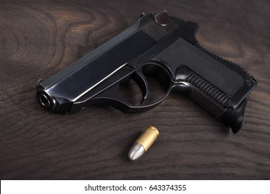 handgun with ammunition on the wooden table