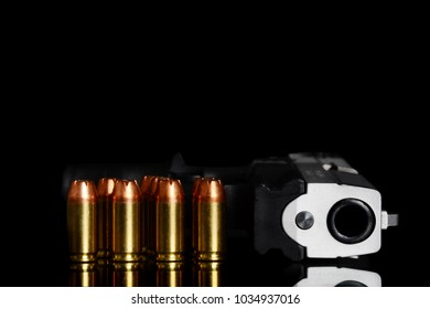 handgun and bullets on glass with black background