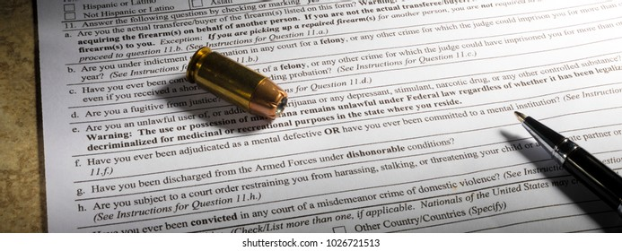 Handgun cartridge and pen with mental health question on gun background check form