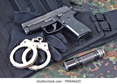 Handgun with handcuffs, gloves and flashlight on black tactical vest and camouflage clothing