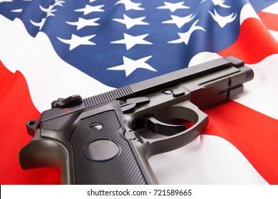 Handgun lying on satin USA flag - close up studio shoot