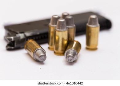 handgun magazine and 9mm bullet isolated over a white background