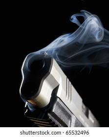 Handgun with its muzzle in the dark with smoke coming out