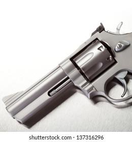 Handgun on brushed metal background, white above