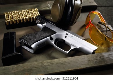 Handgun, pistol CZ Shadow.Gun Parts, cartridges and headphones protecting ears shooting equipment