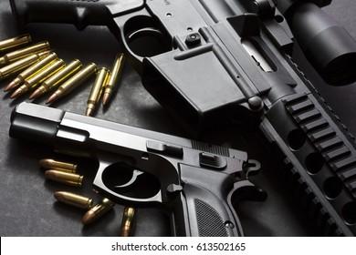 Handgun with rifle over dark background