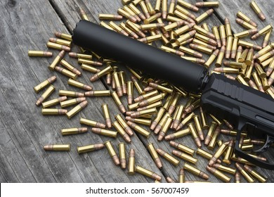 handgun with silencer and pile of ammunition on wooden background
