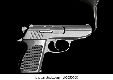 Handgun with smoke emerging from it