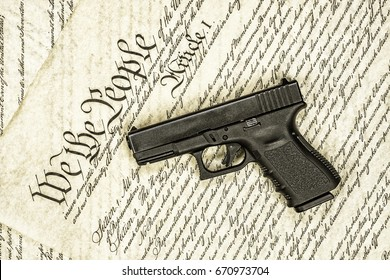 A handgun symbolizing gun rights while framed against the United States constitution.