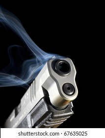 Handgun that is pouring out blue smoke after a shot was taken