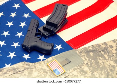 Handgun and US army uniform over US flag. Filtered image: cross processed vintage effect.