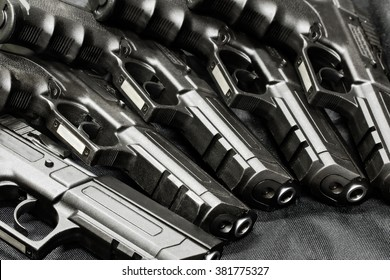 handguns in a row on the black background