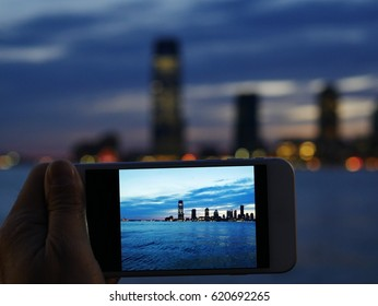 Handheld cell phone camera shooting photo of Jersey City skyline at sunset