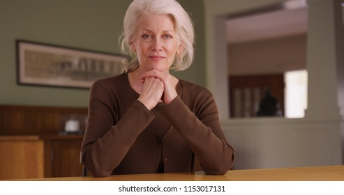 Handheld shot of senior woman homeowner sitting at dining room table