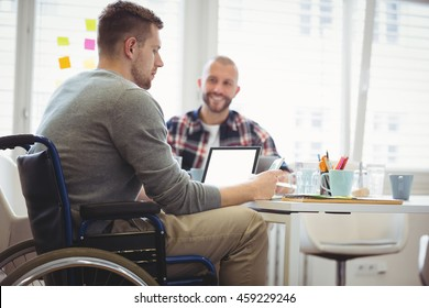 Handicap businessman sitting with colleague in creative office