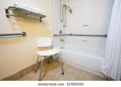 Handicap Hotel Bathroom with Shower Bathtub Hand Rails and a Chair