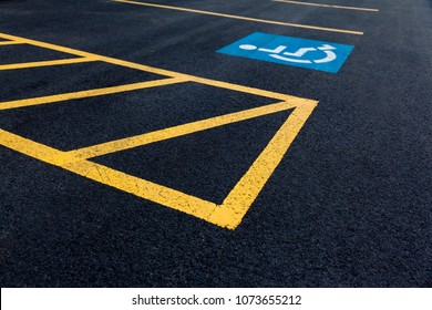 Handicap parking icon on parking lot asphalt with yellow painted lines.