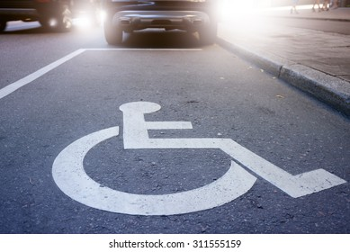 Handicap symbol on road, traffic and pedestrians in background