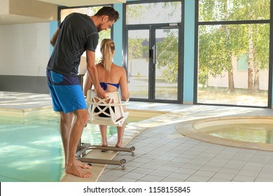 A Handicaped woman on a pool lif at a swimming pool