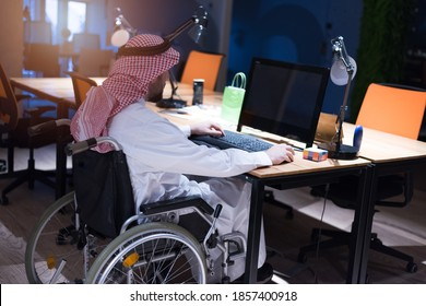 Handicapped Arabic businessman in tradition suit working in office during coronavirus  pandemic. Disabled businessman in the wheelchair works online in the office at the computer.