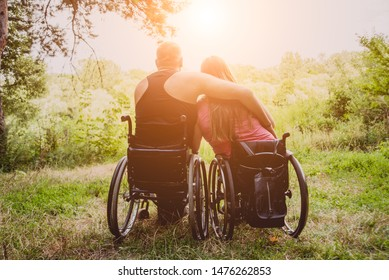 Handicapped couple resting in the forest near lake. Wheelchairs in the forest on the natural background. Camping. Summertime