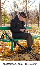 Handicapped elderly man sitting in the park on a wooden bench with his crutches alongside him browsing the internet on a tablet computer