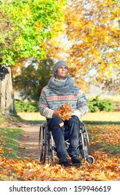 handicapped man in an autumn park sitting in his wheelchair enjoying the peace of being out in nature amongst the colorful yellow trees