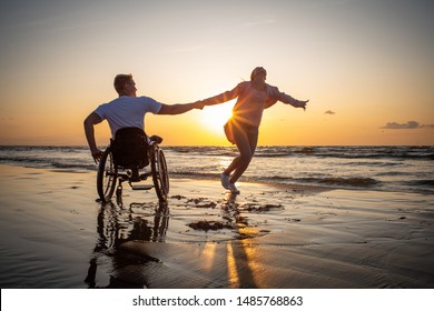 Handicapped man in wheelchair and his girlfriend on a beach at sunset