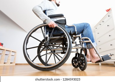 Handicapped man in wheelchair at home.