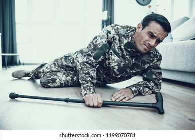 Handicapped Military Lying on Floor with Crutch. Handsome Caucasian Disabled Person in Uniform Fell Down and Try to Get Up in Bright Modern Living Room. Man Feels Strong Pain