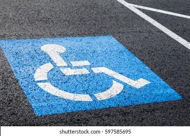 Handicapped parking spot, blue square on black asphalt