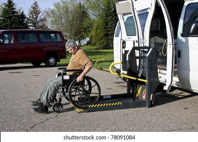 handicapped person backing his wheelchair onto a lift van