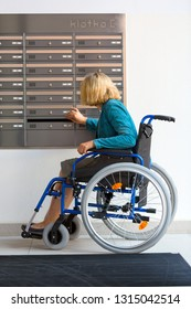 handicapped woman on wheelchair checking mailbox inside the building