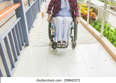 Handicapped woman on wheelchair go to the building using ramp for disabled