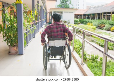 Handicapped woman on wheelchair leaving the building using ramp for disabled