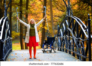 handicapped woman standing ad raising her crutches in the park, wheelchair in the background