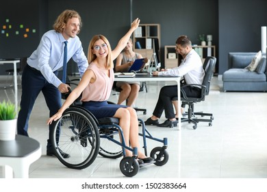 Handicapped young woman with colleague having fun in office
