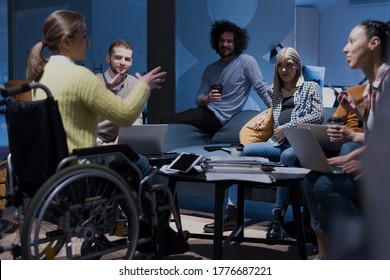 Handicapped young woman with colleagues working in office. She is smiling and passionate about the workflow. Performing in co-working space. Office people working together.