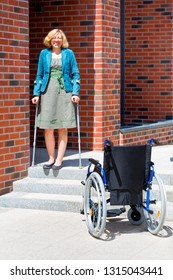 handicapped young woman going down the stairs by herself using crutches