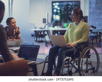 Handicapperd businesswoman in a wheelchair on meeting with her diverse business team brainstorming at office
