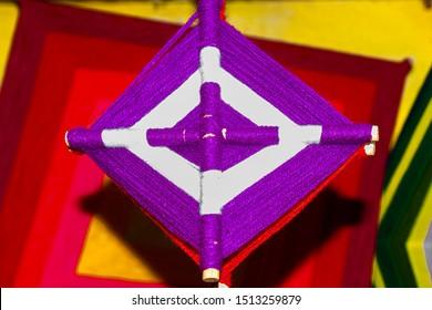 Handicraft called eye of god huichol purple color