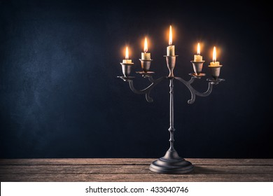 handicraft candelabrum with burning candles on old wooden table against art dark background